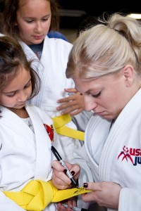 Malia and Makaia Spittel having their belts autographed by Kayla Harrison