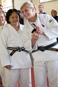 Miki Takemori presenting Kayla Harrison with a special pin owned by her father, Jim Takemori